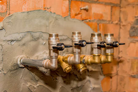Iron taps with a black handle for supplying water in a brick wall of a residential or public building .