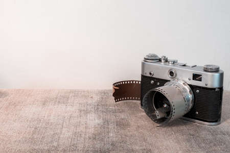 An old film camera and a piece of film on a gray background