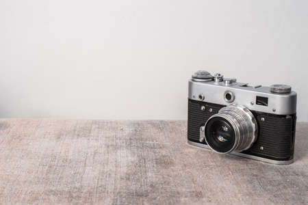 Old film camera on a gray background