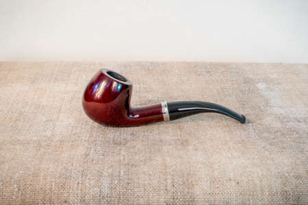 The Smoking pipe is on the table. Gray background.