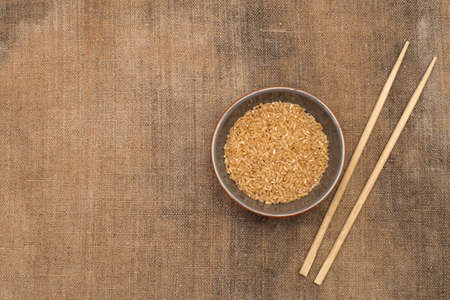 A bowl of rice and wooden chopsticks on sacking. Copy-paste. Space for text