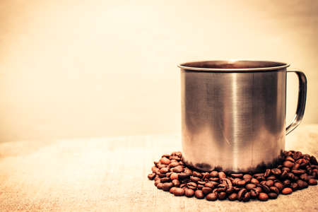 An iron mug stands on coffee beans, a place for text. Copy-paste