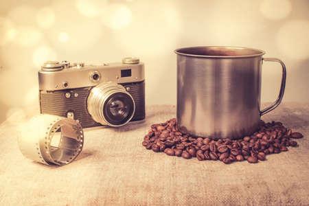 A coffee mug and an old camera. Bokeh effect, tinted photo