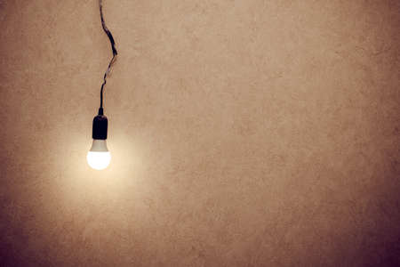 The light bulb is hanging on a wire. Space for text or logo. Banco de Imagens