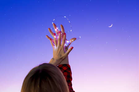 The girl stretches her hands to the starry sky, holding glowing lights. Starry sky and moon