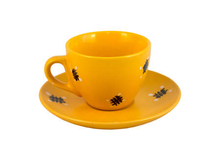 A yellow tea mug with a handle on a yellow saucer. Isolated item on a white background Stock Photo