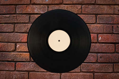 A black gramophone record against a brick wall