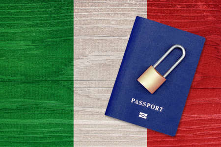 Passport and padlock on the background of the flag of Italy. Ban on leaving the country. Travel abroad is closed. Italian flag and passport. Ban on entering the country Archivio Fotografico