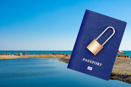 Passport and padlock on the background of the resort and the sea. Ban on leaving the country on vacation. Travel abroad is closed Foto de archivo