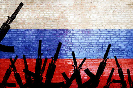 Automatic rifles are raised against the background of the Russian flag. Russian militarism. Armed uprising