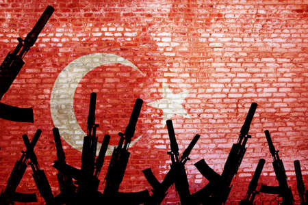 Automatic rifles are raised against the background of the Turkish flag. Turkish militarism. Armed uprising