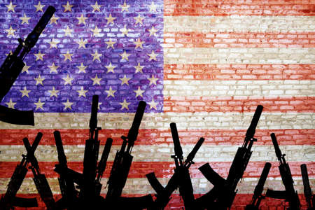 Automatic rifles are raised against the background of the US flag. The militarism of the United States. Armed uprising Stok Fotoğraf
