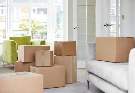 Cardboard carton boxes stack with household belongings in modern house living room. Packed containers on floor in new home.