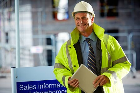 Portrait of smiling mature architect wearing a hardhat and reflective clothing holding a digital tablet on construction site