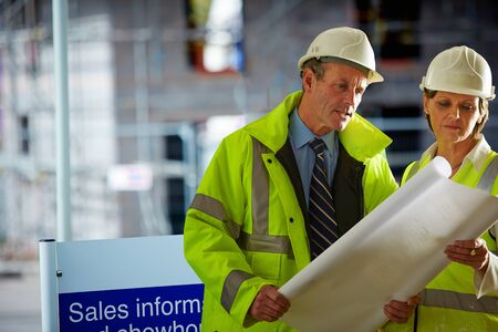 Shot of a two mature architects looking over the blueprints  of a building site