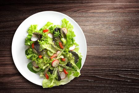 Directly above shot of plate of fresh and healthy salad on wooden background Stockfoto