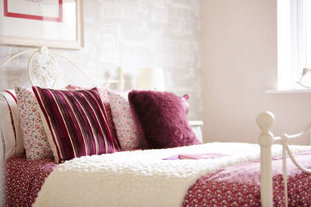 Shot of colorful pillows and bedding on a bed in luxurious bedroom