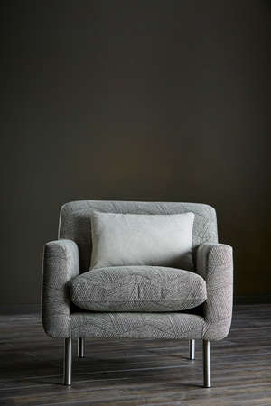 Shot of grey color armchair with pillow on hardwood floor
