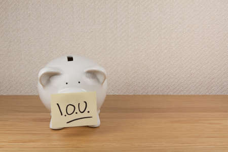 A piggy bank with a note on its nose saying IOU (I Owe You)