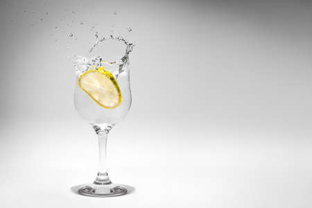 A soda drink splash photographed as a lemon slice falls into the glass.