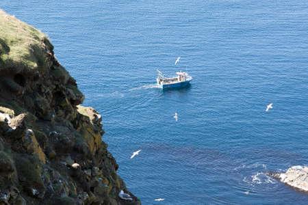 A fishing trawler out at sea near Sumburgh Head in Shetland, North of Scotland, UK.