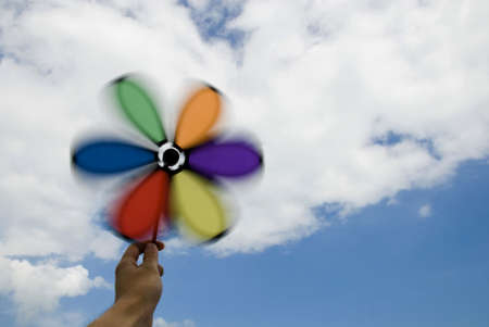 Hand holding spinning wind wheel with cloudy sky