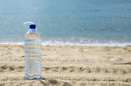 tomando refresco: Botella de agua en la playa