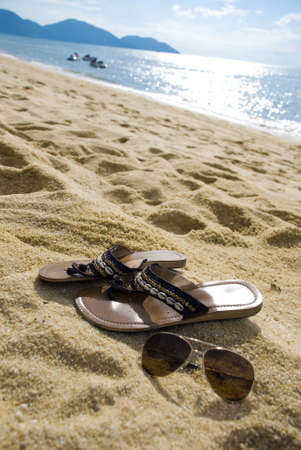 Female sandal and shades on the beach Stock Photo - 3144591