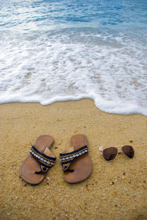 Female sandal and shades on the beach photo