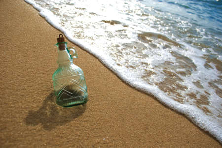 abandoning: Message in bottle lying on beach