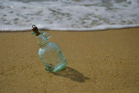 Message in bottle lying on beach photo