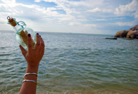 throw up: Throwing bottle into the sea Stock Photo