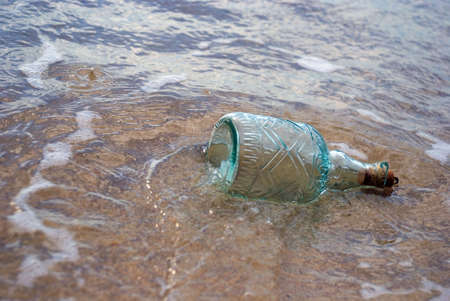 abandoning: Bottle lying a round water on beach