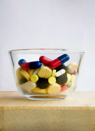 Glass filled fully with medication pills Stock Photo