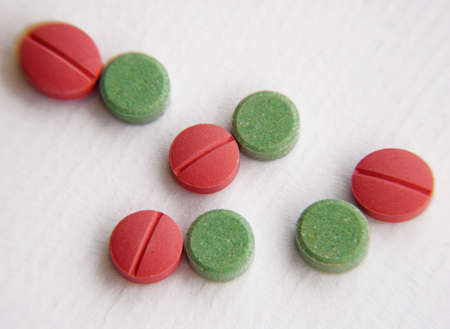 mdma: Green and red tablets on white background