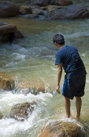 suspense: Asian male hiker looking at raging water, crossing river