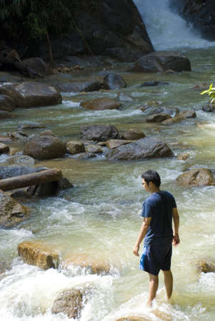 Asian male hiker looking at raging water, crossing river Stock Photo - 3294450