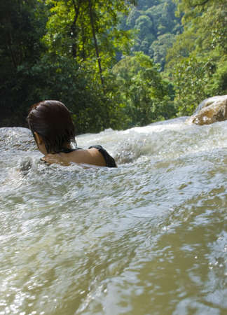 Woman in river heading for waterfall