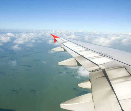 Airplane view - land, sea, sky and plane wing photo