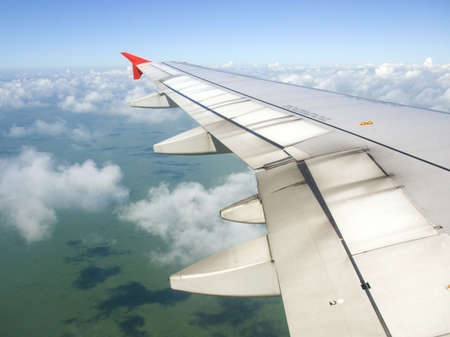 Airplane view - land, sea, sky and plane wing Stock Photo - 3370125