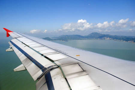 Airplane view - land, sea, sky and plane wing Stock Photo - 3370121