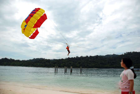 travel features: Parachuting beach sports - young asian girl looking Stock Photo