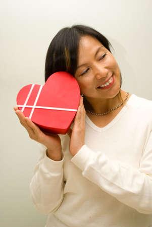 Closing eye enjoying heart shape gift box