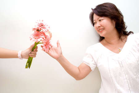 Lady reaching out for pink gerbera flowers Stock Photo