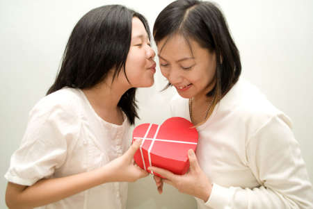 Daughter passing gift to mum and kissing her photo