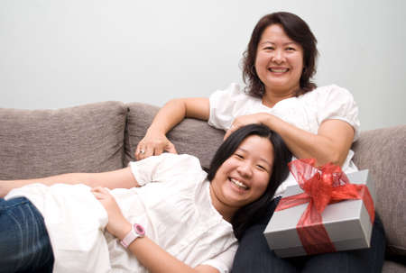 Happy mother and daughter relaxing on couch photo