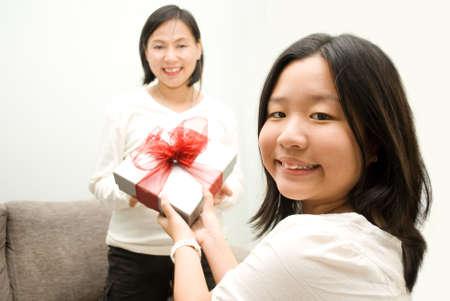 Daughter passing gift to mum Stock Photo - 4411608