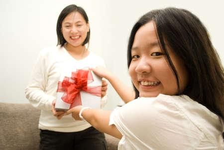 kinfolk: Daughter giving mum a gift Stock Photo