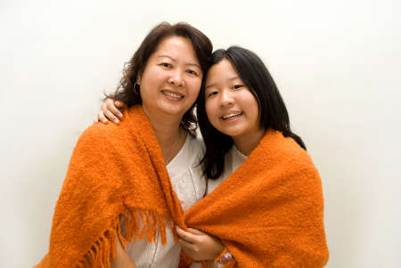 Mother and daughter wrapped in orange blanket Stock Photo