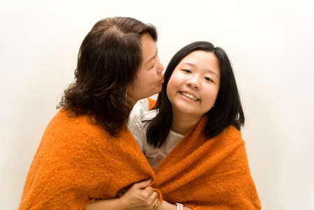 Mother kissing daughter wrapped in blanket Stock Photo - 4411713